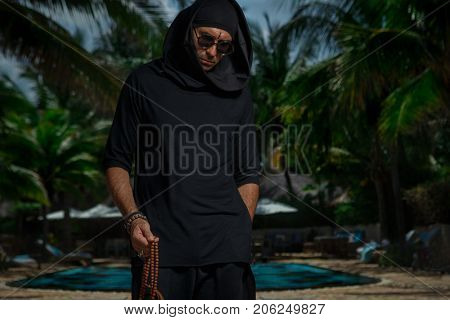 Freak in black clothe and glasses holding buddhist rosary