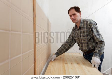 Construction worker installing a wooden countertop in a domestic kitchen