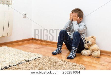 Sad little boy with teddy bear sitting on floor in room