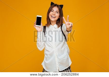 Smiling teenage schoolgirl in uniform with backpack holding blank screen mobile phone and showing peace gesture isolated over orange background