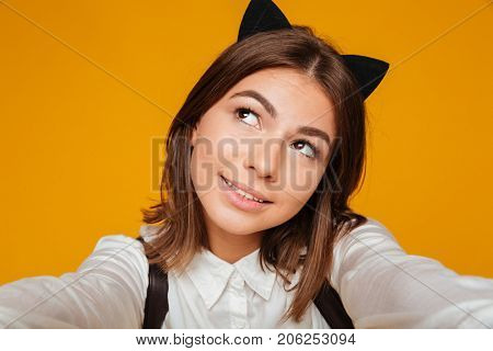 Close up portrait of a cute teenage schoolgirl in uniform with backpack taking a selfie while standing and looking away isolated over orange background