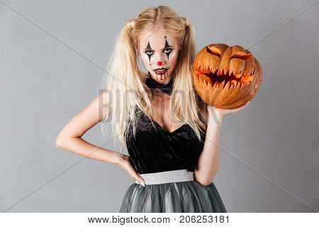 Attractive blonde woman in halloween clown make-up and blood streaks holding curved pumpkin and looking at camera isolated over gray background