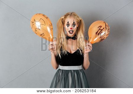 Excited crazy blonde woman in clown make-up holding halloween balloon isolated over gray background