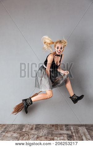 Full length portrait of a laughing crazy blonde woman in halloween clown make-up and blood streaks riding a broom while jumping isolated over gray background