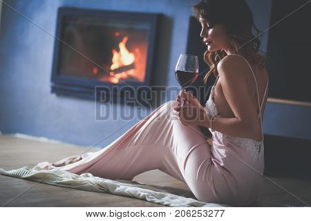 Sexy woman in front of the fireplace. Wood fireplace.