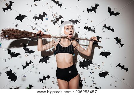 Portrait of a pretty young woman in halloween cat costume posing with a broom over bats and confetti background