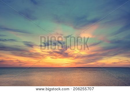 Aerial panoramic view of sunset over ocean. Nothing but sky, clouds and water. Dramatic picturesque evening scene. Ocean and colorful cloudy sky in the background. Nature landscape. Travel background