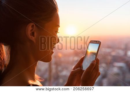 Woman tourist looking at phone pictures of sunset view of Europe travel destination. Asian girl using cellphone camera app in London Shard Tower, UK. Mobile photography taking photos.