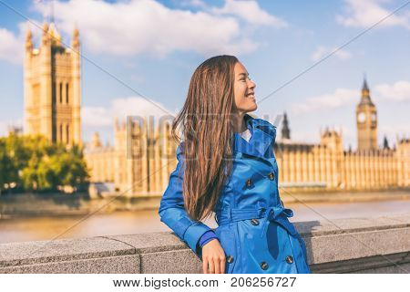 London city lifestyle Asian businesswoman Europe autumn travel in blue trench coat. Multiracial model posing in fashion fall outerwear at Westminster and Big Ben, famous european urban destination.