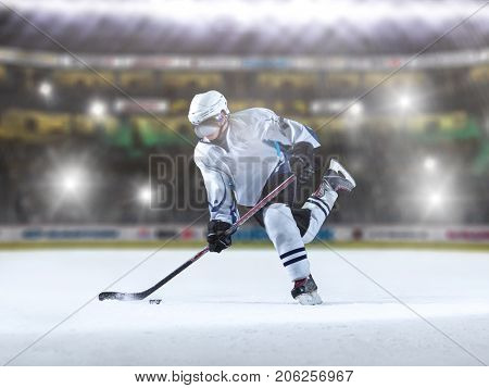 ice hockey player in action kicking with stick in front of big modern hockey arena with flares and lights