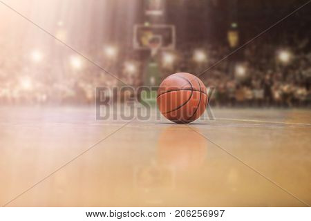 Basketball ball,  board and net in front of big modern basketball arena