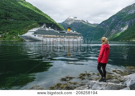 Cruise liner in the fjord. Girl on the shore of the Geirangerfjord near the town of Geiranger, Norway