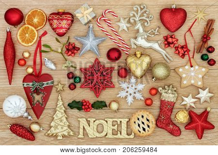 Christmas symbols with noel sign, bauble decorations, traditional ornaments, holly, mistletoe, mince pie and gingerbread biscuit on oak wood background.