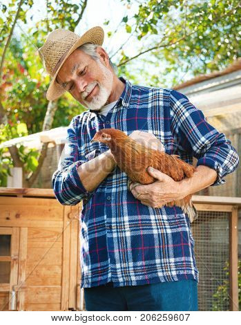 Happy organic farmer holds chicken in his arms in front of hen house