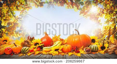 Thanksgiving background with pumpkins, wooden plank and falling leaves