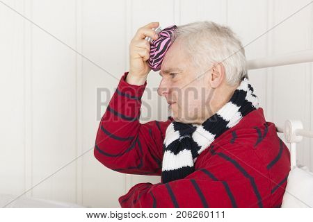 Senior sick man sitting in bed with ice pillow against head ache