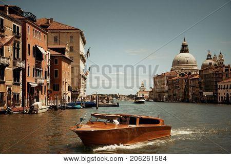 Busy Venice canal and Church Santa Maria della Salute in Italy.