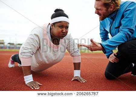 Dedicated sport trainer encouraging overweight young woman try harder while practicing push-ups