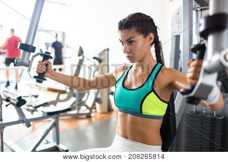 Sporty girl making effort while doing exercise for arm muscles on special equipment