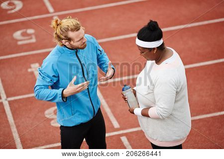 Run instructor giving recommendations to young sporty plump woman before marathon