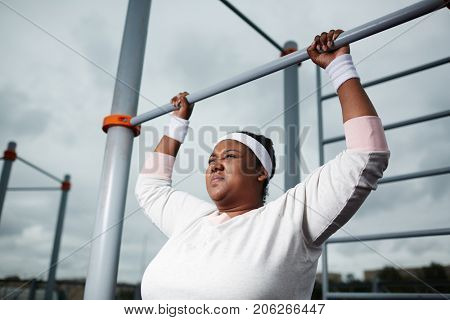 Persistant chubby girl trying to do difficult exercise while hanging on bar of outdoor sport facilities