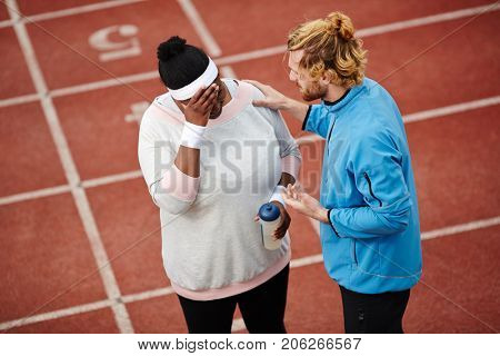 Professional sport instructor encouraging and supporting anxious over-size female after workout on stadium before marathon