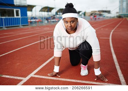 Young oversized competitor of marathon standing by line at low start on racetrack and waiting for signal to run
