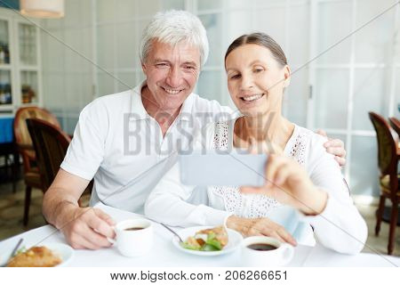 Affectionate senior spouses making selfie by cup of coffee in cafe