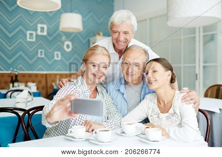 Friendly seniors making selfie in cafe during get-together