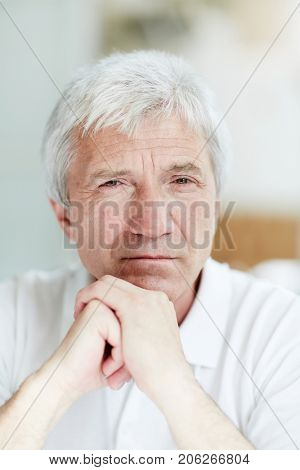Calm man of retirement age staring at camera with his hands on chin