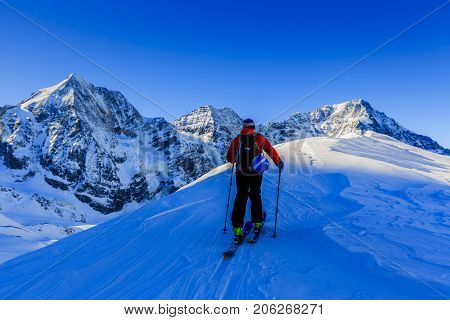 Mountaineer backcountry ski spring walking up along a snowy ridge with skis. In background blue cloudy sky and shiny sun and Tre Cime, Drei Zinnen in South Tirol,