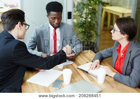 Profile view of confident young entrepreneur sitting at boardroom table and conducting negotiations with business partners