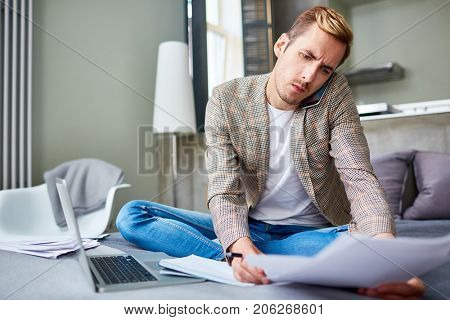 Concentrated young freelance worker sitting on cozy bed while talking to his colleague on mobile phone and taking necessary notes, interior of studio apartment on background