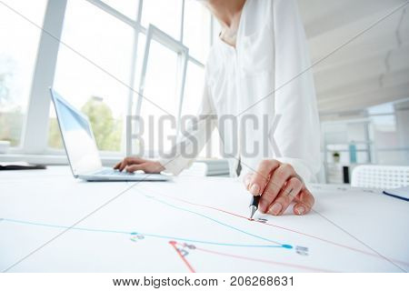 Concentrated young white collar worker standing at desk and analyzing business graph indicating corporate progress, interior of spacious open plan office on background