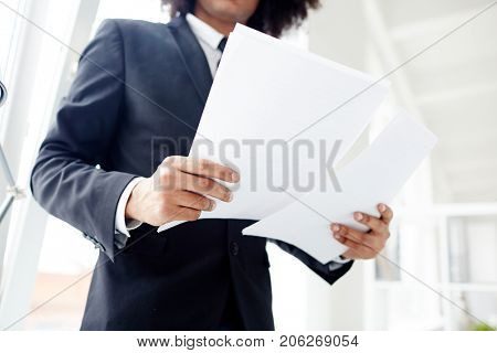 Low angle view of unrecognizable manager wearing suit studying documents while standing at open plan office, close-up shot