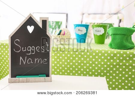 Small chalkboard with text SUGGEST NAME on table at baby shower party