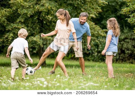 Mother plays football soccer with family in summer
