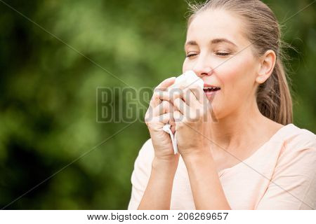 Woman with a cold sneezing from allergy or hay fever