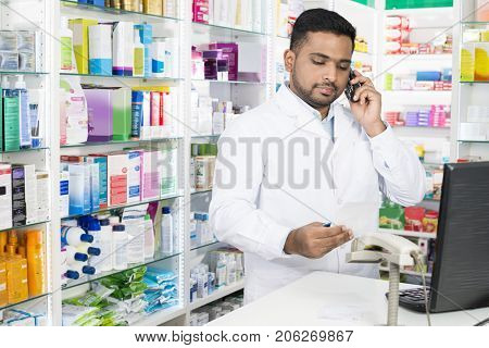 Confident Pharmacist Using Phone While Holding Prescription Pape