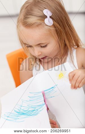 Little girl involved in a hand crafting project - using safety scissors to cut a paper sheet - closeup, shallow depth