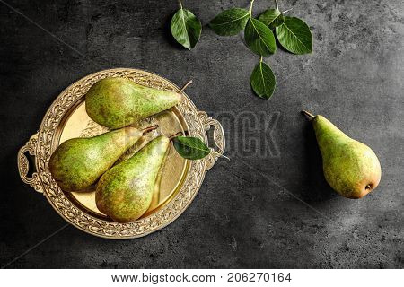 Composition with ripe pears and ornate metal plate on dark background
