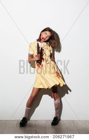 Full length image of crazy zombie woman in dress with knife looking at the camera over white background