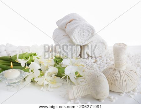 Lying on Branch ginger flower on three rolled towel,bottle oil with herbal ball ,candle on pile of white stones