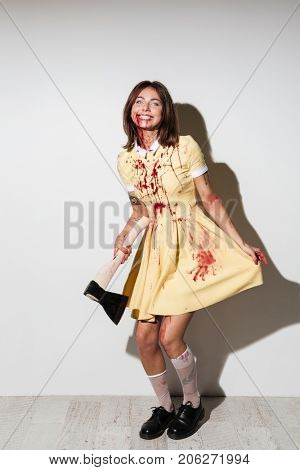 Full length image of happy zombie woman in dress posing with an axe and looking at the camera over white background