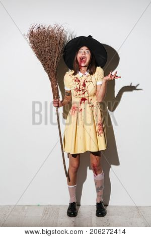 Full length image of screaming woman in halloween costume holding broom and looking at the camera over white background