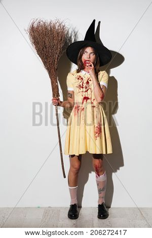 Full length image of serious pensive woman in halloween costume holding broom and looking away over white background
