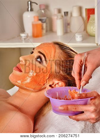 Collagen face mask . Facial skin treatment. Woman receiving cosmetic procedure in beauty salon. Bottle with moisturizing cream on background. Masks for skin tightening.