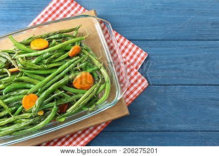 Delicious green beans and carrot slices in glass baking dish on table