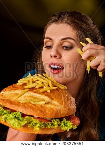 Woman eating french fries and hamburger. Student consume fast food. Girl bite of slice. Girl trying to eat a lot of junk. Advertise fast food on black background. French fries lies on the hamburger.