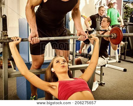 Fitness friends workout gym. Woman working on bench press. She lifting barbell. Trainer backs girl while taking exercises. Group work people on treadmill background. Couple trains together.